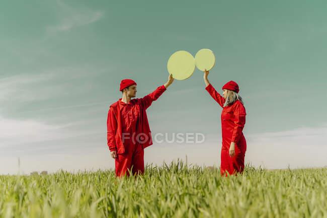 Pareja joven vestida con monos rojos de pie en un campo con dos círculos verdes - foto de stock