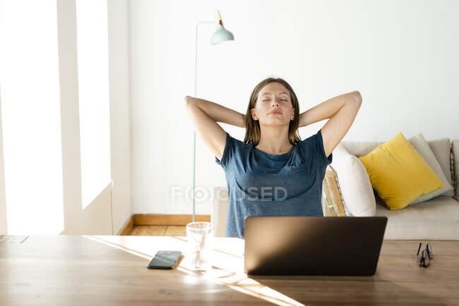 Молодая женщина дома расслабляется и отдыхает от работы за ноутбуком в домашнем офисе — стоковое фото