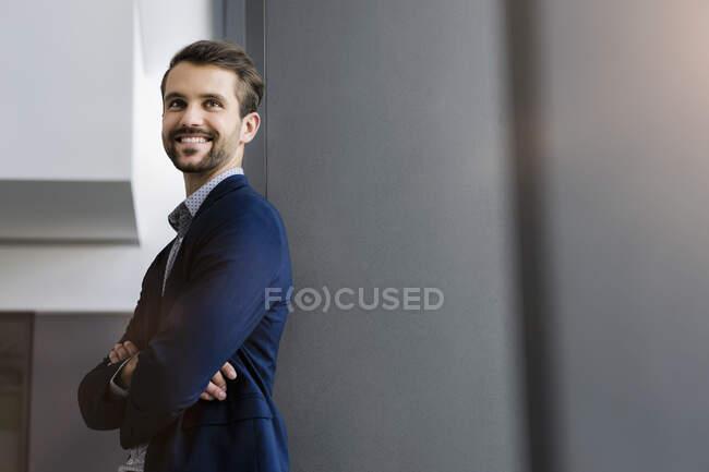 Retrato de joven empresario feliz mirando a la distancia - foto de stock