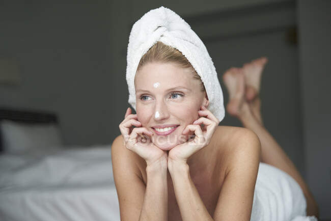 Портрет прекрасної жінки з головою загорнута в рушник лежачи на ліжку — стокове фото