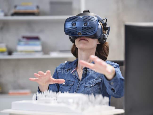 Mujer con gafas VR y auriculares en la oficina moderna - foto de stock