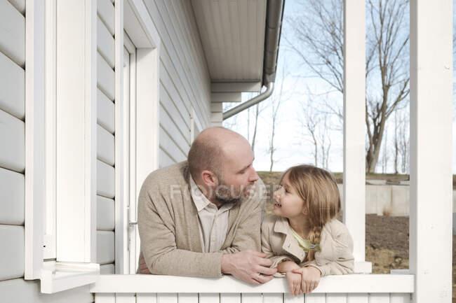 Pai e sua filha sorridente no alpendre de sua casa — Fotografia de Stock