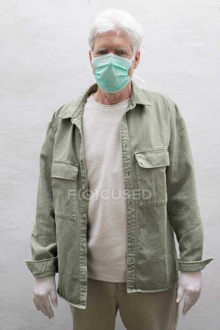 Homem sênior usando máscara facial e máscara protetora — Fotografia de Stock