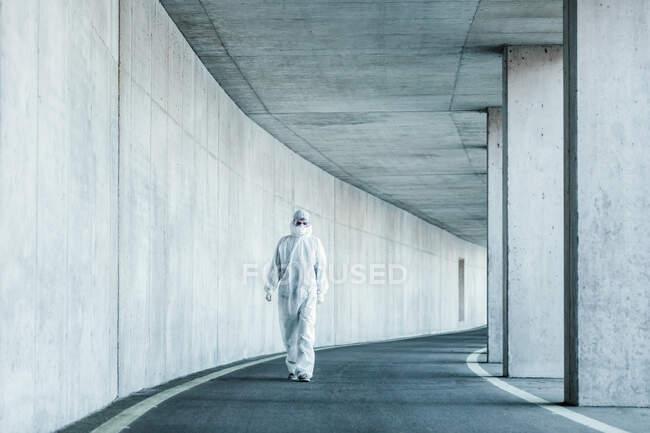 Чоловік у захисному одязі, який ходить тунелем. — стокове фото