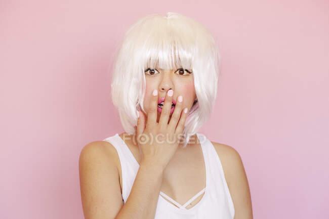 Портрет переляканої молодої жінки з закритим ротом перед рожевим фоном. — стокове фото