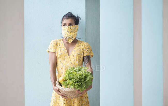 Mujer con cesta de sujeción de tela bucal con ensalada y frutas frescas - foto de stock