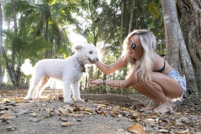 Hermosa mujer jugando con su perro en la playa, Costa Rica - foto de stock