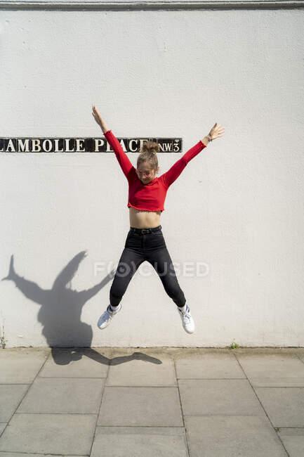 Mujer joven exuberante saltando frente a una pared - foto de stock