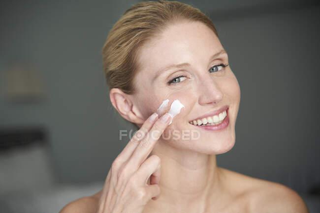 Retrato de mujer hermosa feliz aplicando crema en su mejilla - foto de stock