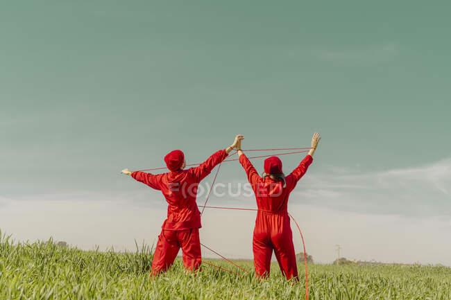 Vista posterior de la joven pareja con monos rojos y sombreros actuando en un campo con hilo rojo - foto de stock