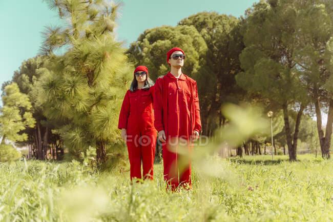 Pareja joven vistiendo monos rojos y sombreros de pie en la naturaleza - foto de stock