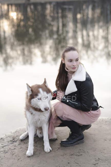 Retrato de la mujer y su husky en el borde del agua - foto de stock