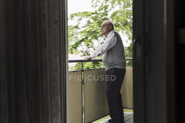 Homem sênior de pé na varanda olhando para a distância — Fotografia de Stock