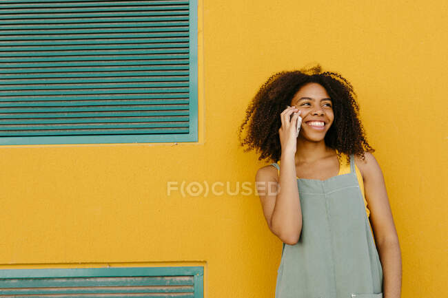 Portrait of happy young woman wearing overalls in front of yellow wall talking on the phone — Stock Photo