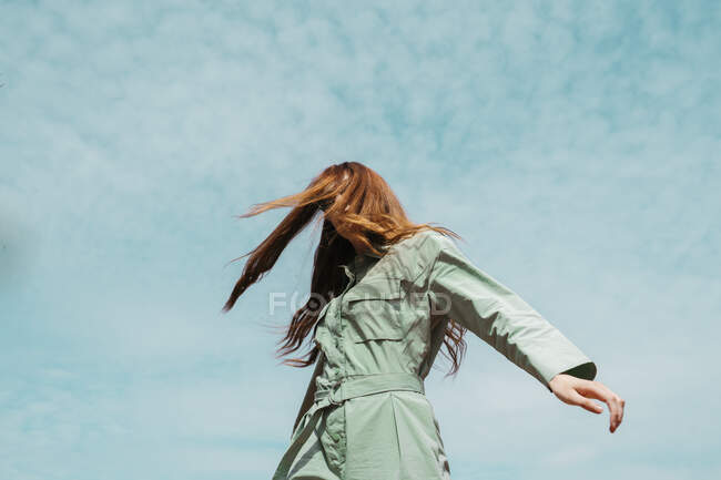 Redheaded young woman dancing in front of sky — стокове фото