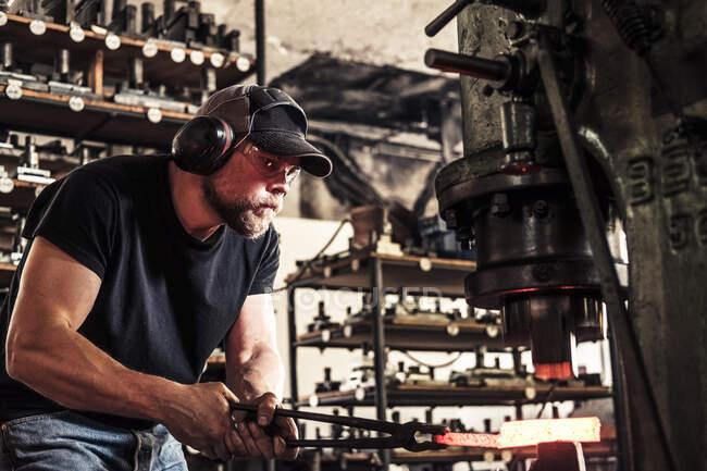 Fabricante de facas trabalhando com aço damasco no martelo hidráulico — Fotografia de Stock