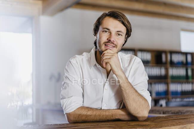 Portrait of confident businessman in wooden open-plan office — Stock Photo