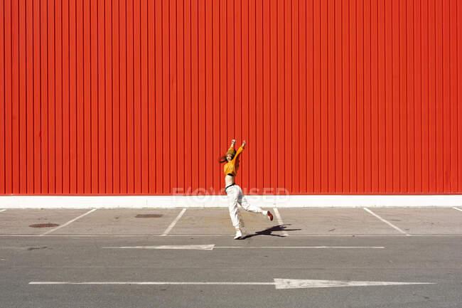Молодая женщина танцует перед красной стеной — стоковое фото