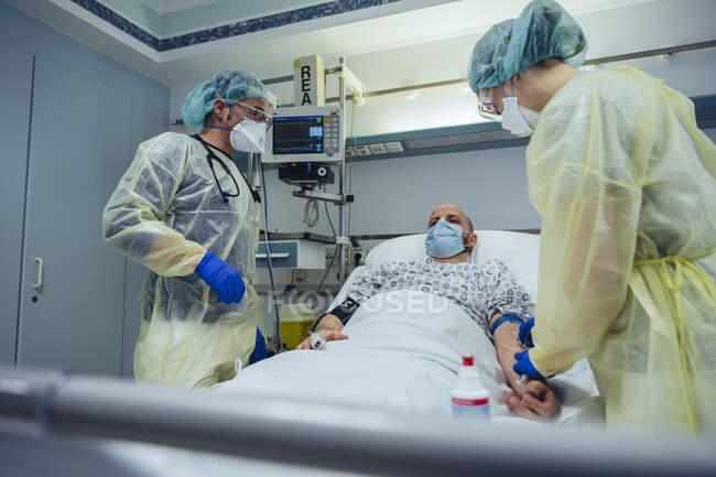 Médicos que cuidam de pacientes em unidades de emergência de um hospital que recolhe amostras de sangue — Fotografia de Stock