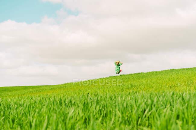 Vista posteriore della donna vestita di verde su un campo che salta in aria — Foto stock