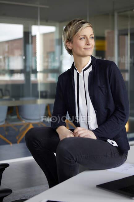 Довірлива комерсантка сидить за столом у кабінеті. — стокове фото