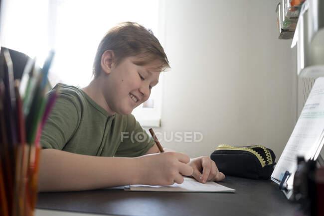 Smiling boy sitting at desk at home doing homework — Stock Photo