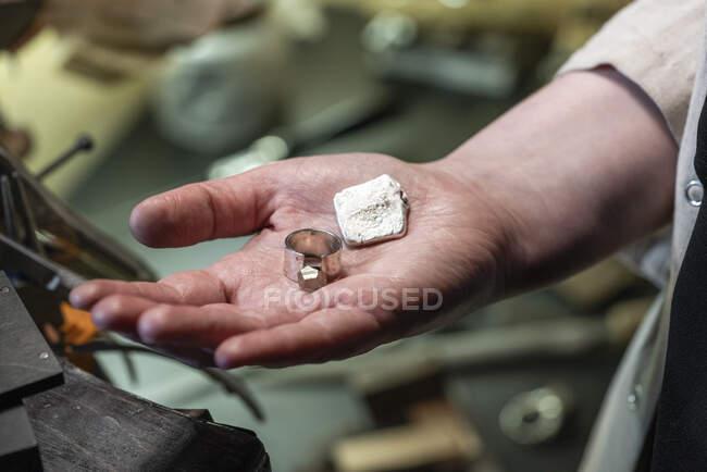 Feminino ourives mostrando anel de prata acabado — Fotografia de Stock
