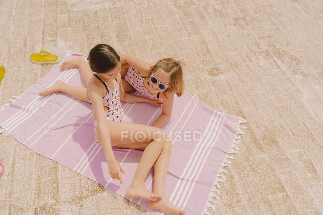Two girls in swimsuits lying on blanket — Stock Photo