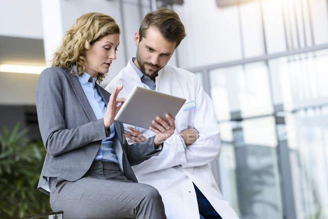 Безробітна жінка з планшетом і лікарем розмовляє в лікарні. — стокове фото