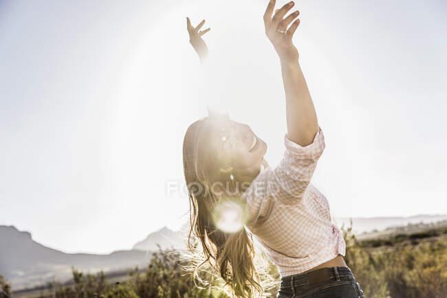 Mujer de pelo largo bailando en el campo al atardecer - foto de stock