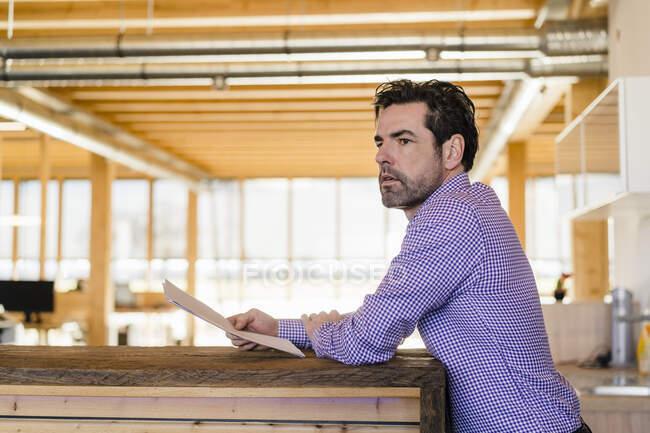 Бизнесмен, держащий бумаги в деревянном офисе открытой планировки — стоковое фото