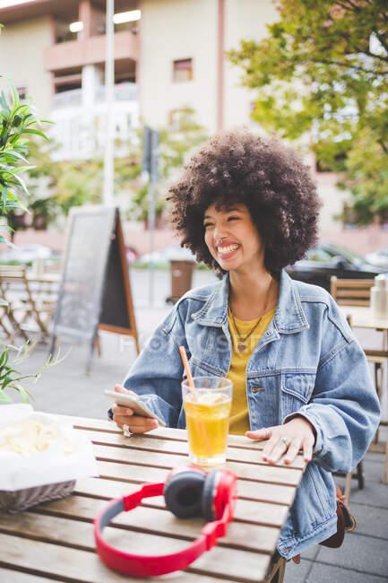 Счастливая молодая женщина с афро-прической в уличном кафе в городе — стоковое фото