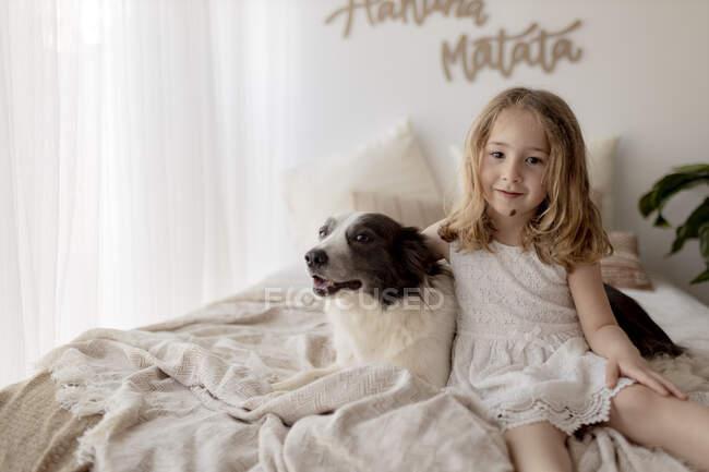 Retrato de niña sentada en la cama con su perro - foto de stock