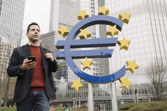 Uomo d'affari premuroso utilizzando il telefono cellulare mentre in piedi contro la scultura e la Banca centrale europea — Foto stock
