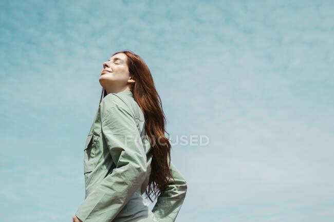 Retrato de una joven pelirroja con los ojos cerrados contra el cielo - foto de stock