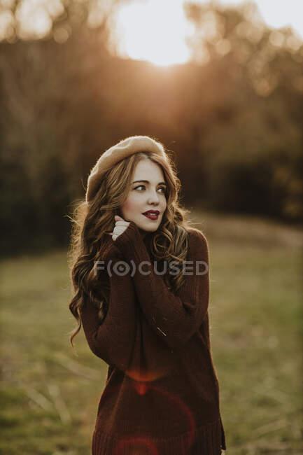 Retrato de mulher na moda em pé em um prado no backlight — Fotografia de Stock