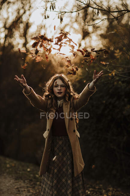 Retrato de mulher na moda jogando folhas de outono no ar — Fotografia de Stock