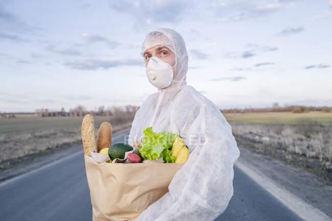 Homem vestindo terno protetor e máscara segurando saco de supermercado em uma estrada rural — Fotografia de Stock