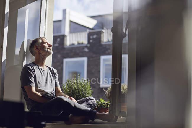 Hombre maduro sentado en la ventana de casa con los ojos cerrados - foto de stock