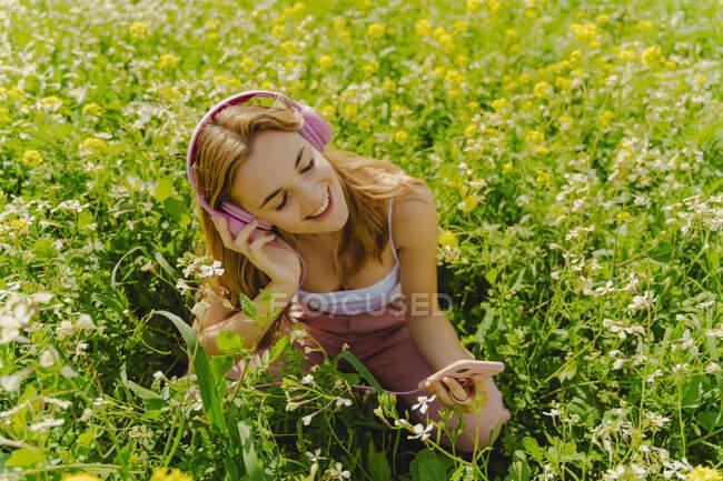 Mujer joven feliz con auriculares y teléfono inteligente en un prado de flores en primavera - foto de stock