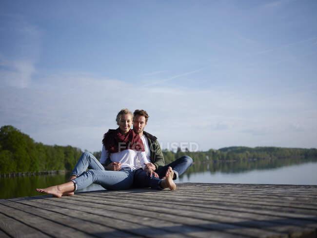 Coppia romantica seduta sul molo al lago — Foto stock