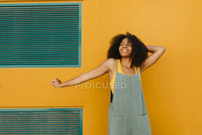 Porträt einer glücklichen jungen Frau in Overalls vor gelber Wand — Stockfoto
