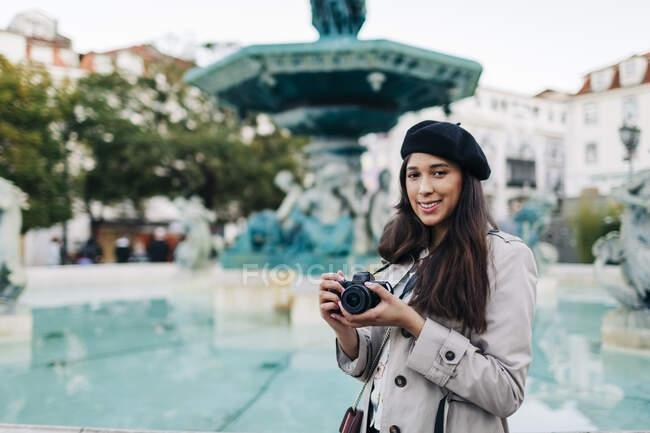 Jóvenes viajeras con cámara en la fuente de la plaza Rossio, Lisboa, Portugal - foto de stock
