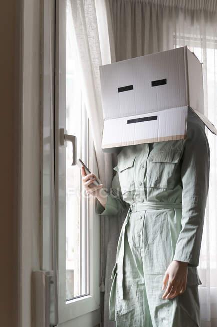 Donna che indossa una scatola di cartone in testa con sorriso annoiato guardando fuori dalla finestra e utilizzando smartphone — Foto stock