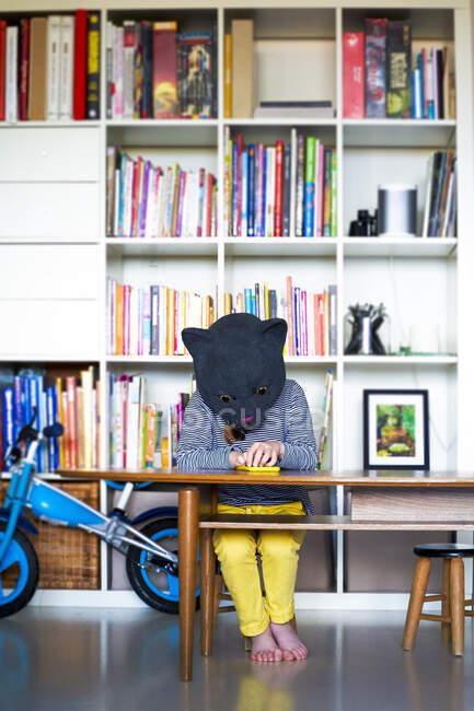 Little girl wearing cat mask, using smartphone — Stock Photo