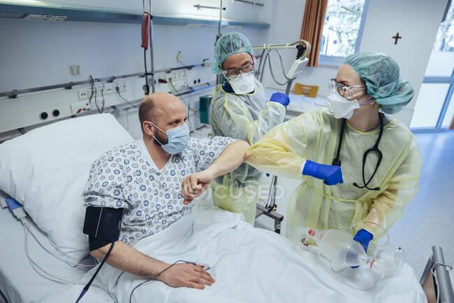Médicos que fazem colisão de cotovelo com o paciente curado na unidade de emergência de um hospital — Fotografia de Stock