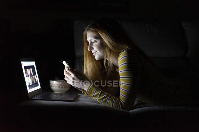Mujer joven tumbada en el sofá en casa usando el ordenador portátil y el teléfono inteligente - foto de stock