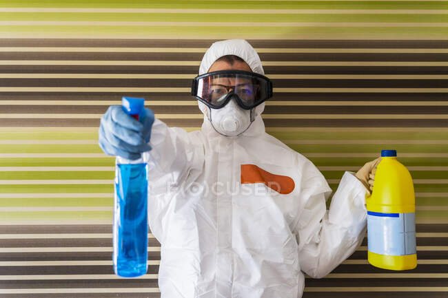 Woman wearing protective clothes, sanitizing her home — Stock Photo