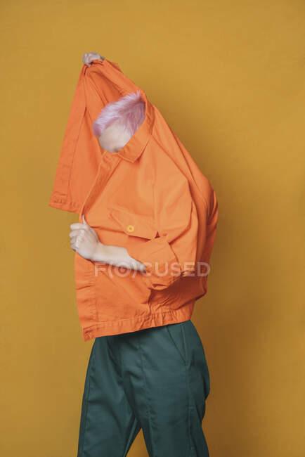 Giovane donna con i capelli corti rosa che indossa giacca arancione davanti a sfondo giallo — Foto stock