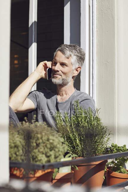 Hombre maduro hablando por teléfono en la ventana de casa - foto de stock